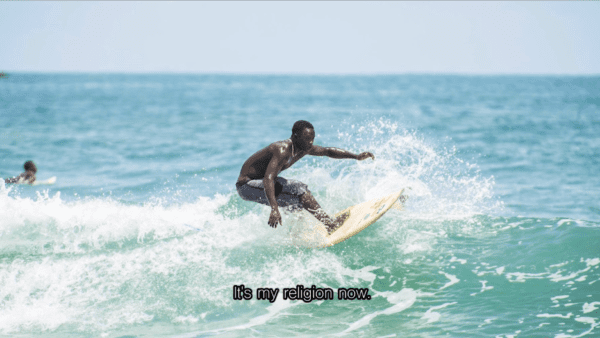 "African surfer catches a wave with the caption ""it is my religion now."""