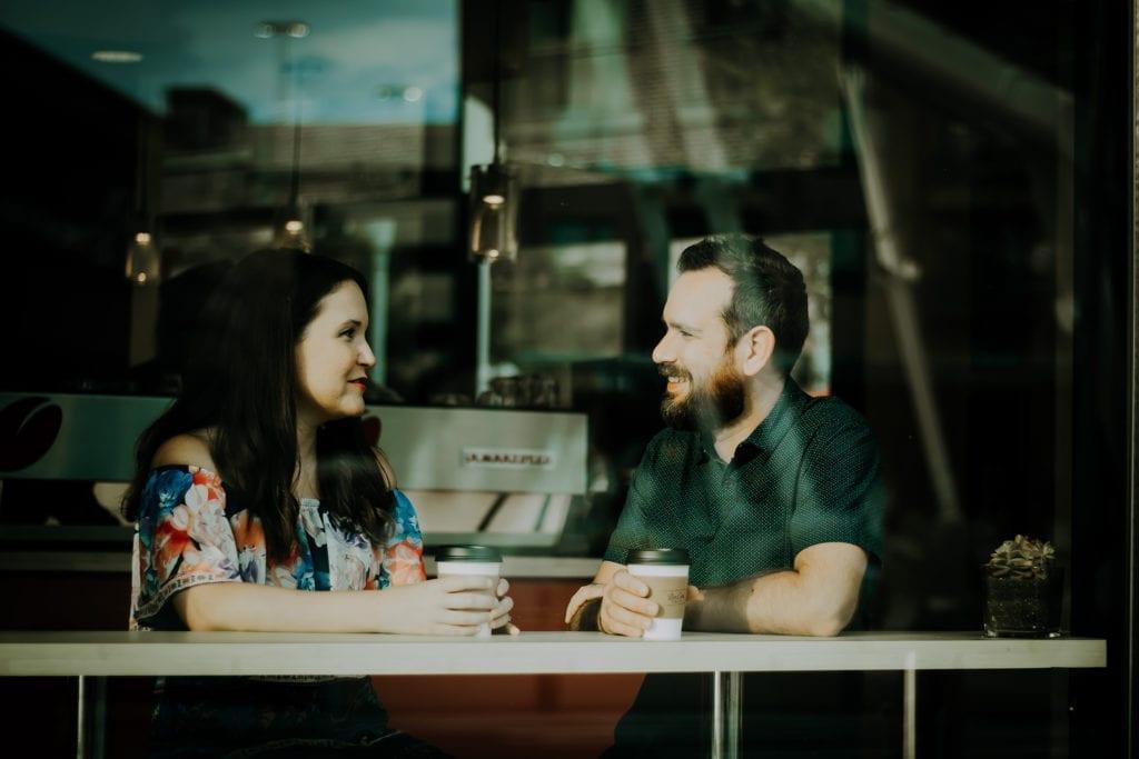 man and woman talk in coffee shop seen through window