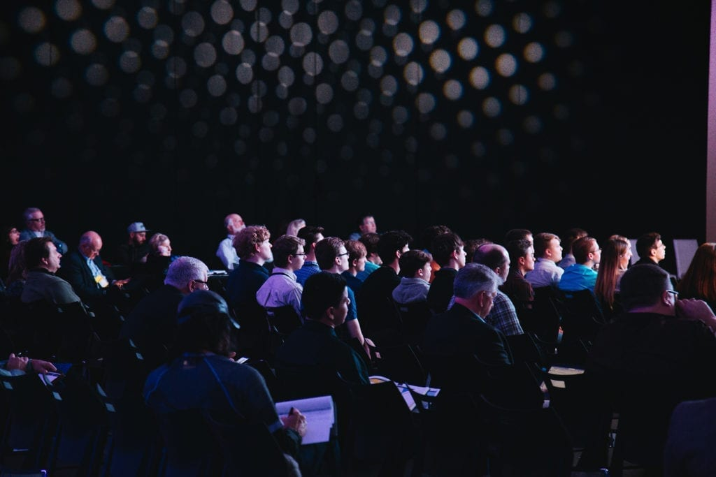 people in darkly lit room at a conference taking notes listening to a speaker