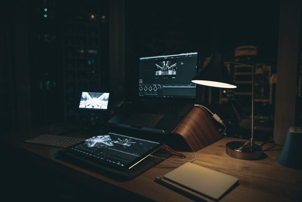 vide =o colorist editing equipment on wooden desk with multiple monitors and lamp