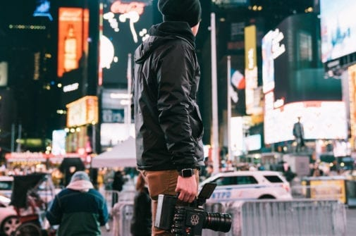 mN STANDS IN TIMES SQUARE WITH A RED CAMERA FILMMAKER