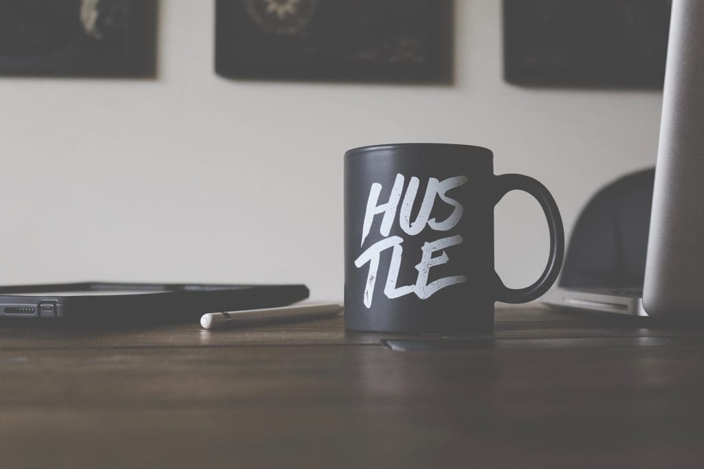 black mug with white script text that says hustle on a wooden table