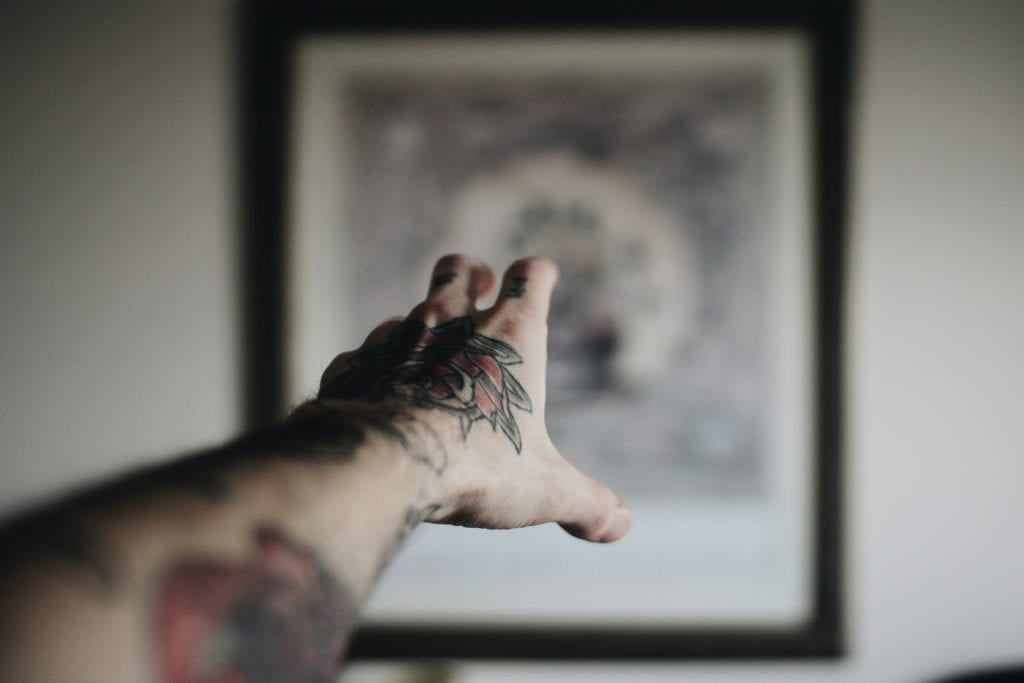 tattoo hand reaches toward painting point of view