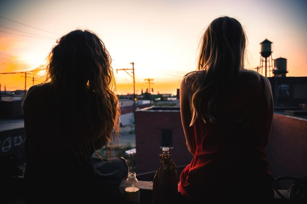 friends sit on rooftop with drinks watching sunset