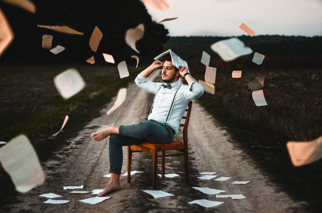 man sitting on dirt road with paper flying everywhere