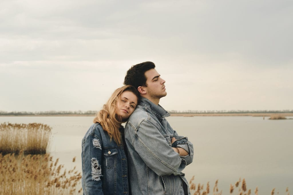 man and woman in denim jackets stand by bay