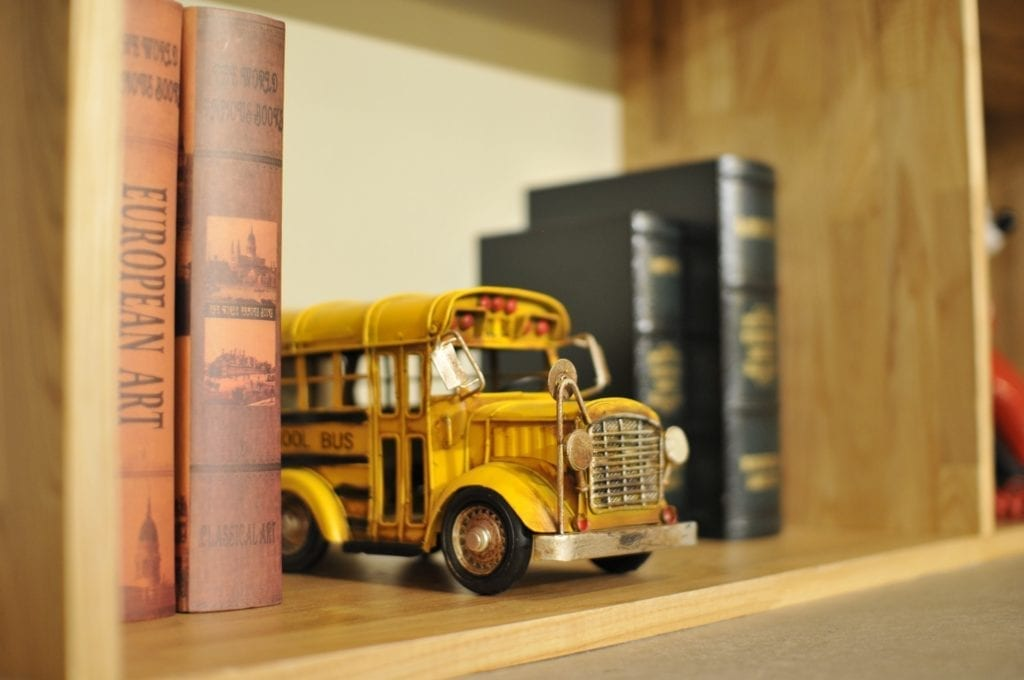 school bus toy on bookshelf