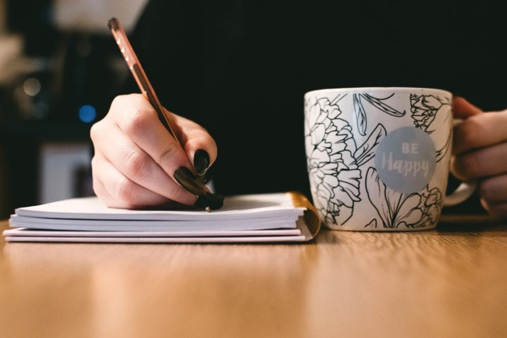 woman writing screenwriting notes with pen