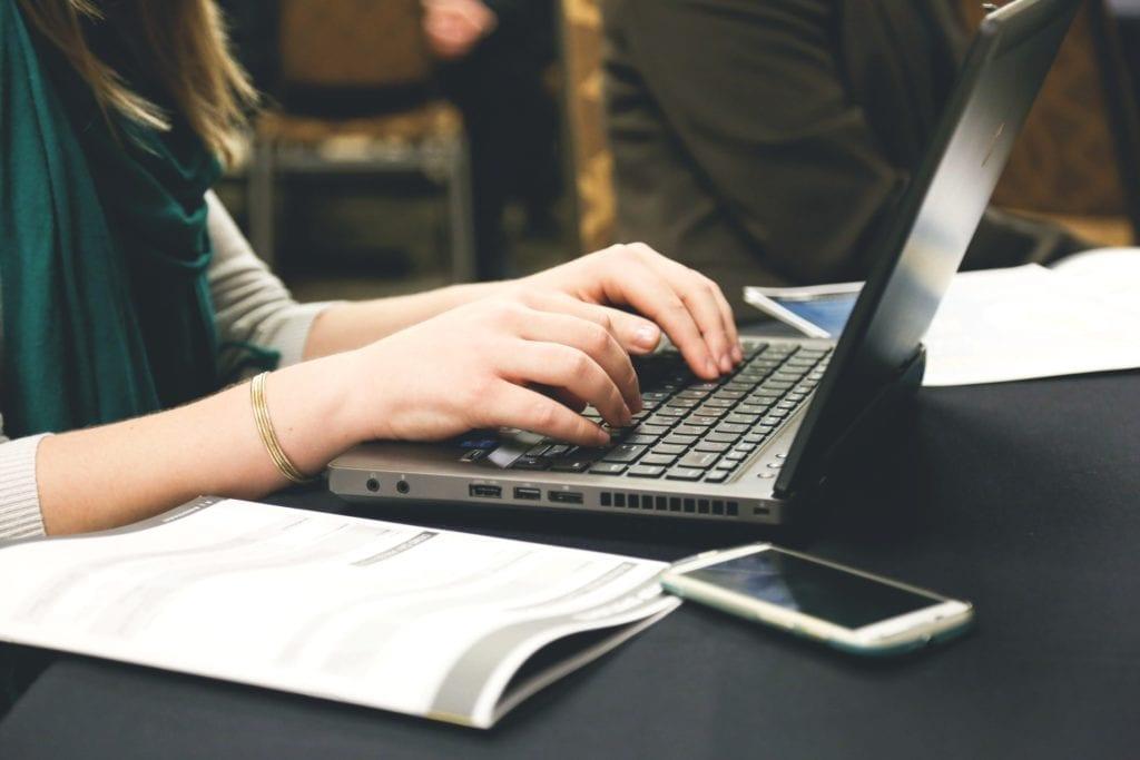 woman taking screenplay notes at laptop
