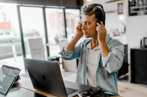 digital producer sitting at laptop with headphones