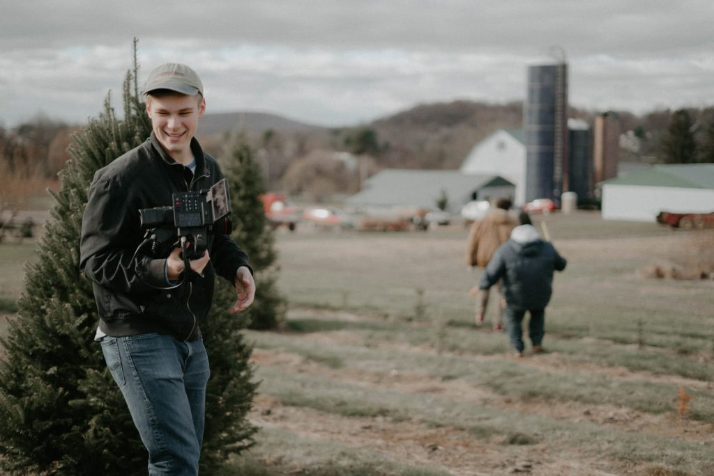 filmmaker exterior shot film producer in front of christmas tree