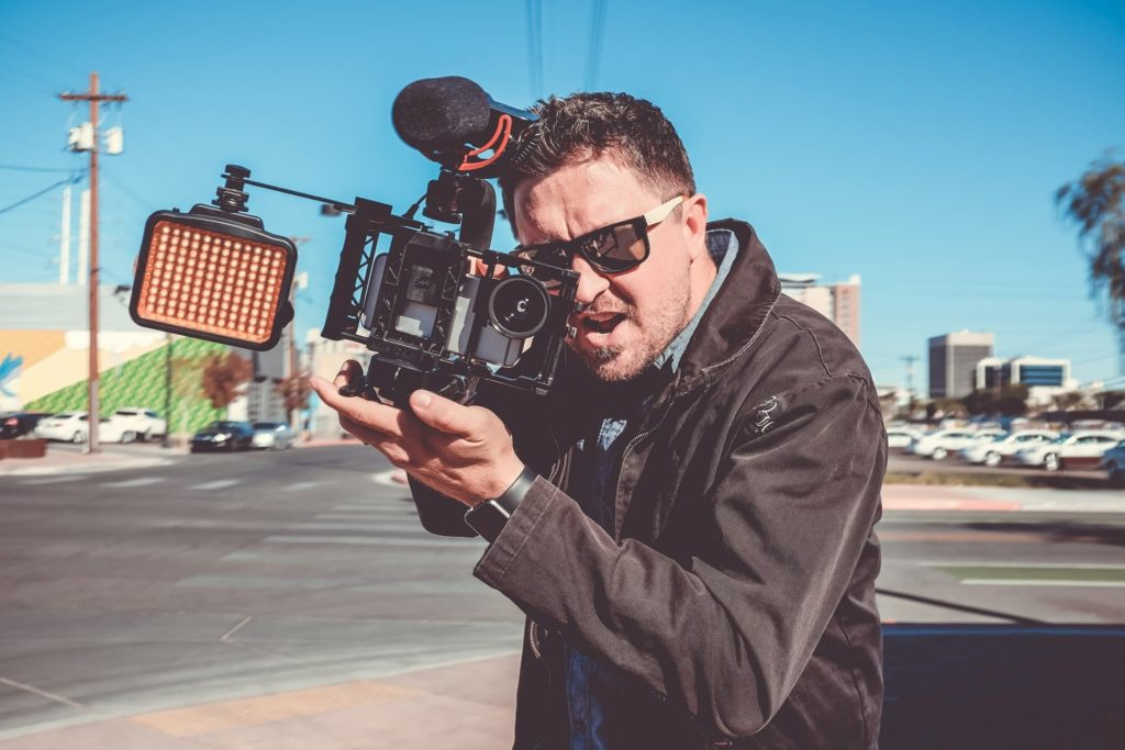 filmmaker holding camera wearing sunglasses