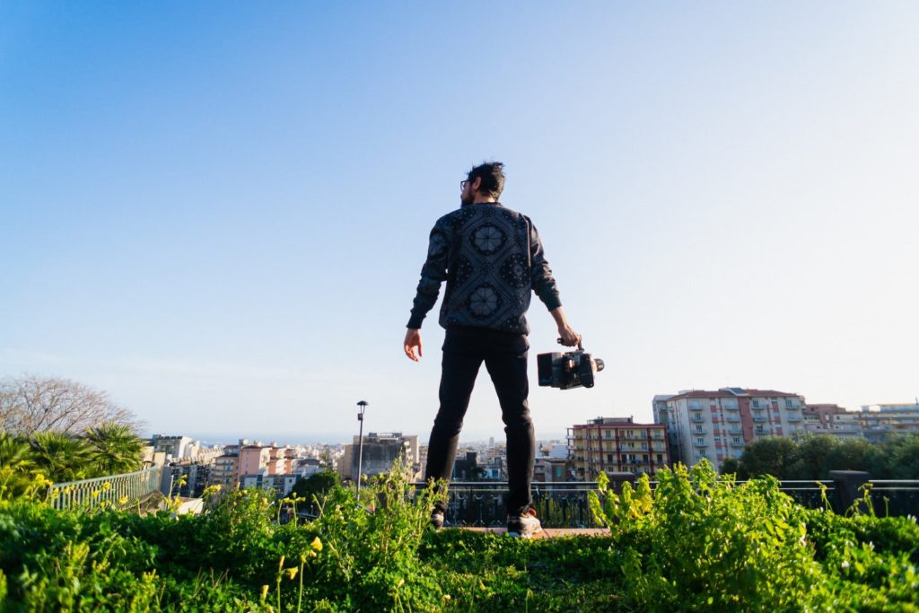 filmmaker holding camera on grassy hill