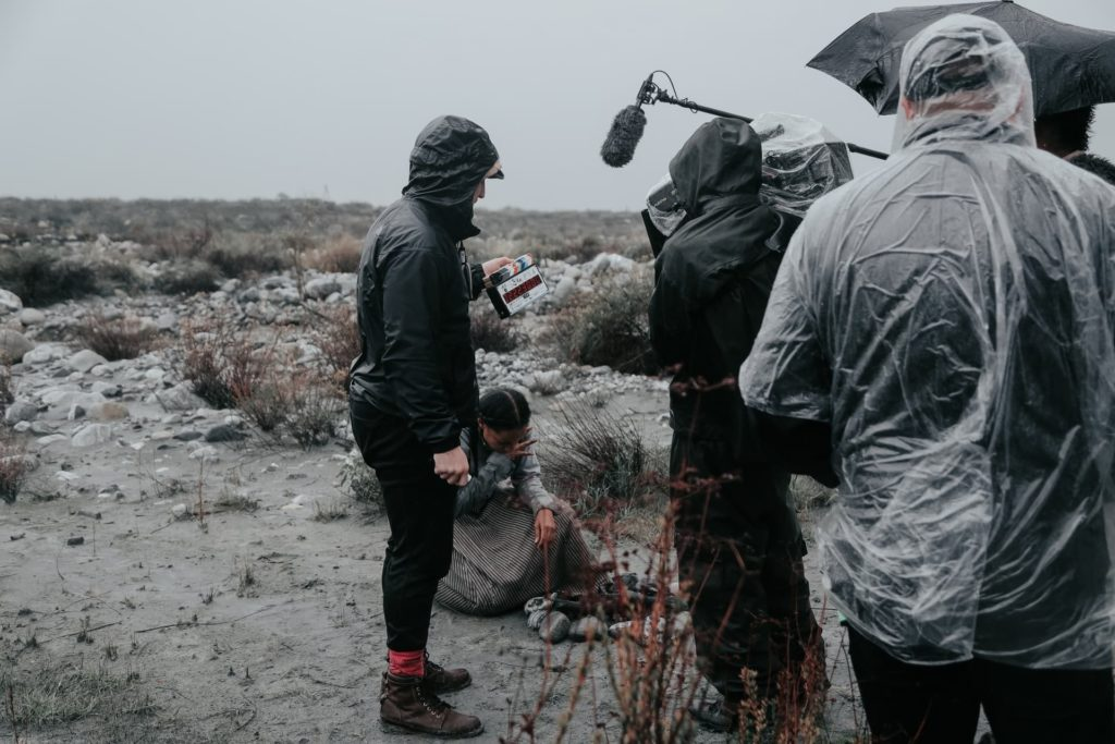 producer wearing rain jacket poncho on film set