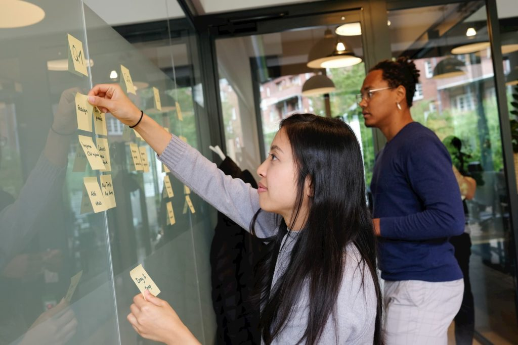 A girl creating an outline with postit notes