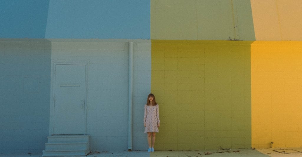 Woman standing in front of colored wall film fund.