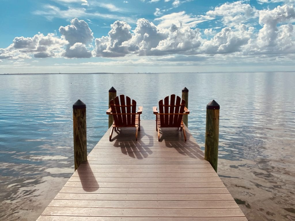 Adirondack chairs set up on a pier film fund.
