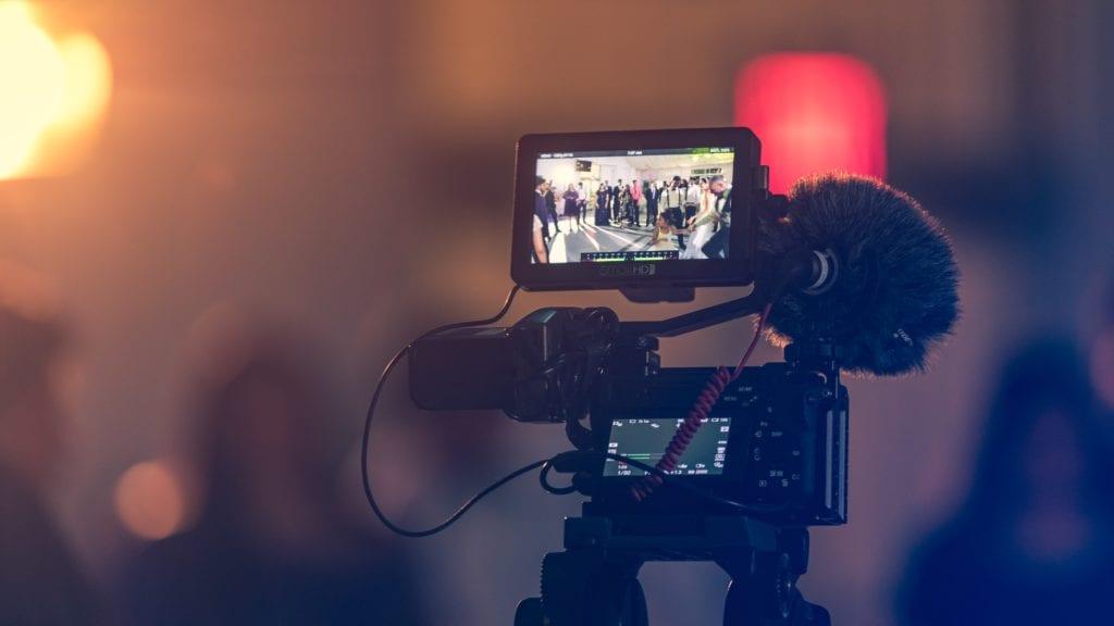 Video monitor displays wedding guests dancing on the dance floor film fund.
