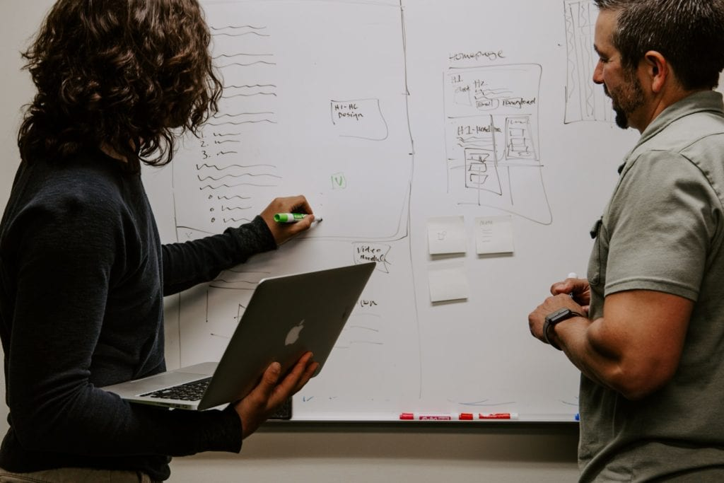 two individuals having a discussion by a white board the film fund