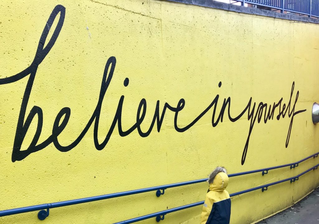 person standing in front of wall that says 'believe in yourself' the film fund