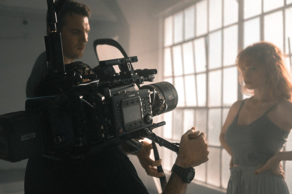 two men working to adjust the camera as they film a woman the film fund