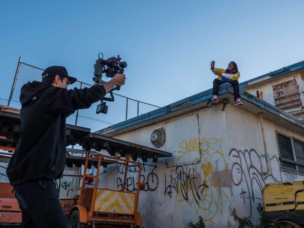 man filming person sitting on roof the film fund